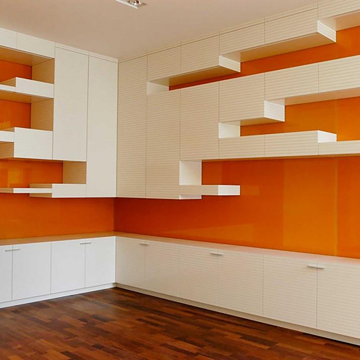 Byt Praha 1 - obývací stěna v lakované bílé barvě v kombinaci s oranžovým sklem.