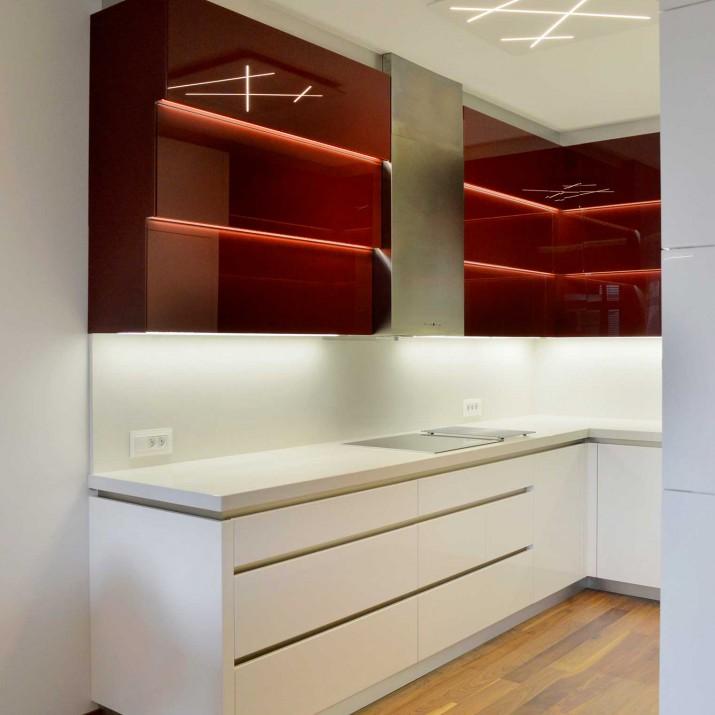 Byt Praha Barrandov - kuchyně v bílém laku ve vysokém lesku v kombinaci s bordó sklem.