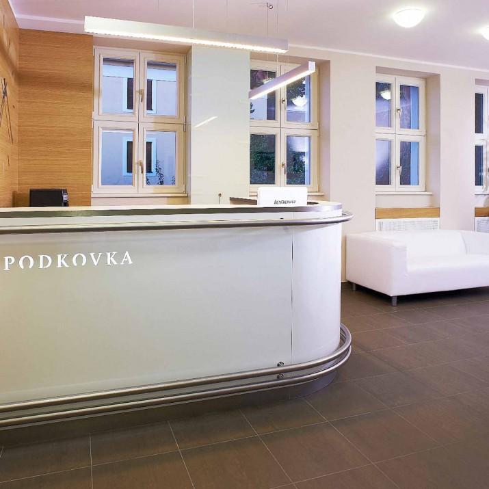 Ordinace Podkovka Praha Podolí - recepce s dubovým obkladem a vestěnými hodinami.