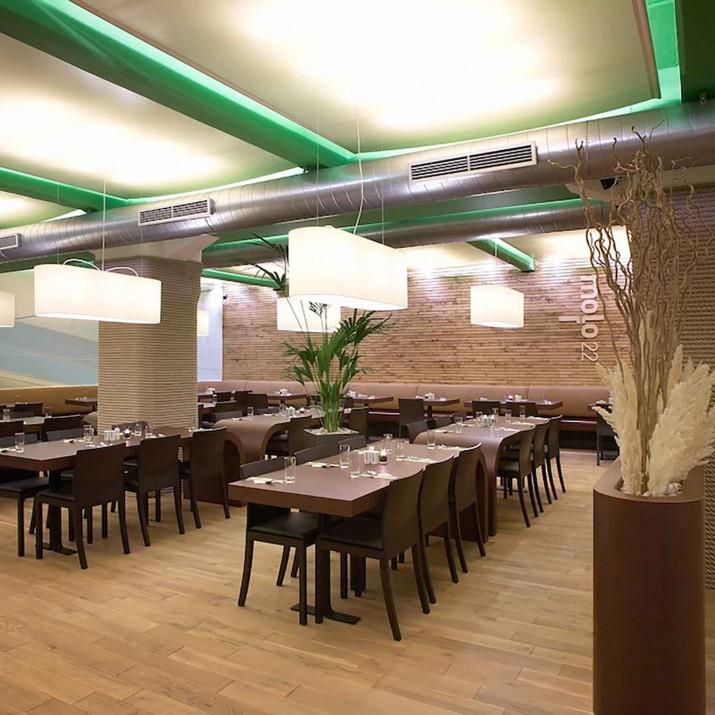 Restaurace Mollo 22 Praha Holešovice - ohýbané stoly, čalouněné lavice a kulaté květináče.