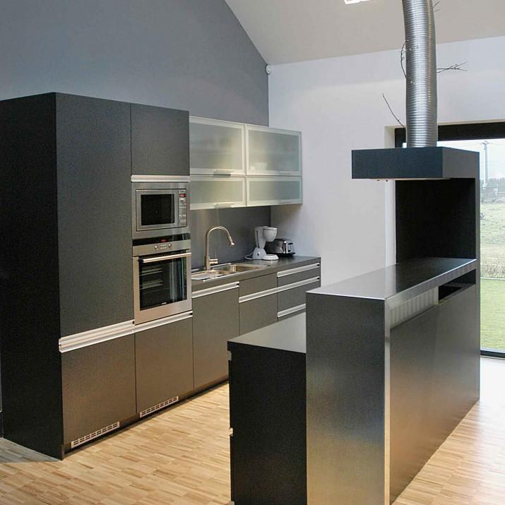 Rodinný dům Kostelec u Křížku - kuchyně z tmavého laminátu se zajímavým odvodem digestoře.