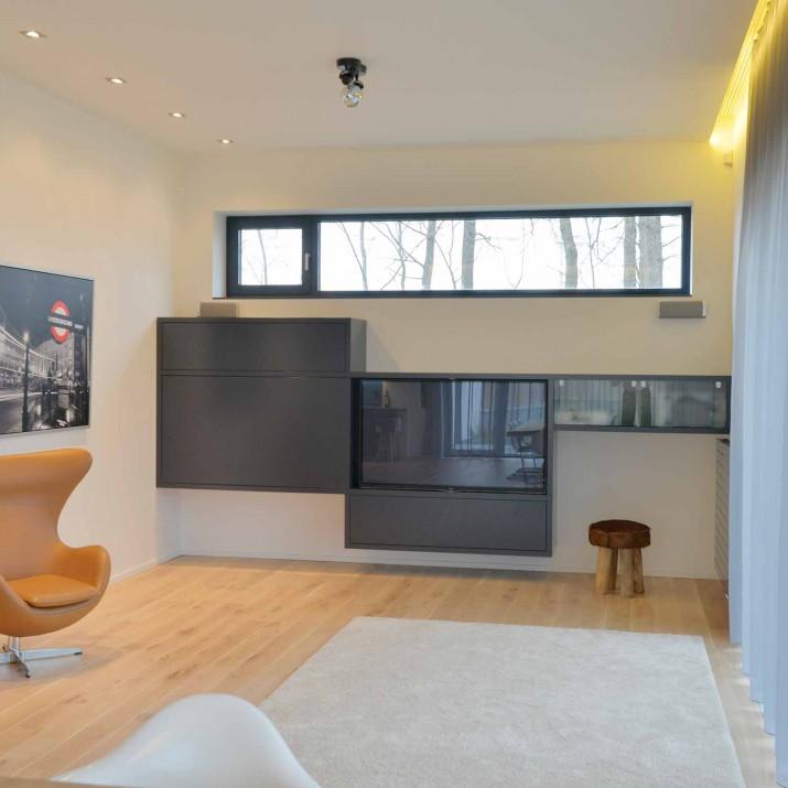 Rodinný dům Praha Chabry - lakovaná obývací stěna se skrytou TV.