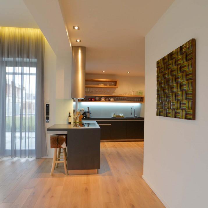 Rodinný dům Praha Chabry - kuchyně z tmavého laminátu v kombinaci se sukatým dubem.
