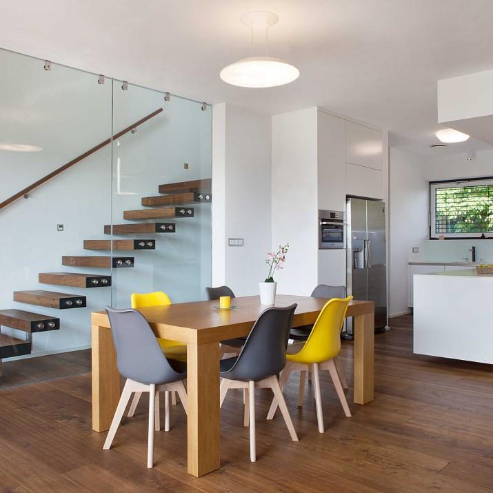 Rodinný dům Praha Řeporyje - pohled na schodiště, kuchyni a jídelní stůl.