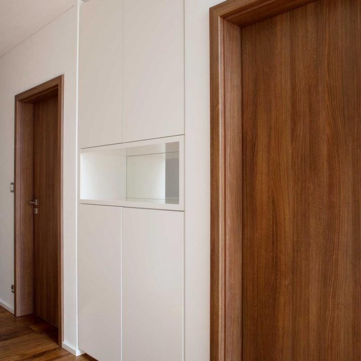 Rodinný dům Praha Řeporyje - lakovaná skříň v nice se zrcadlem.