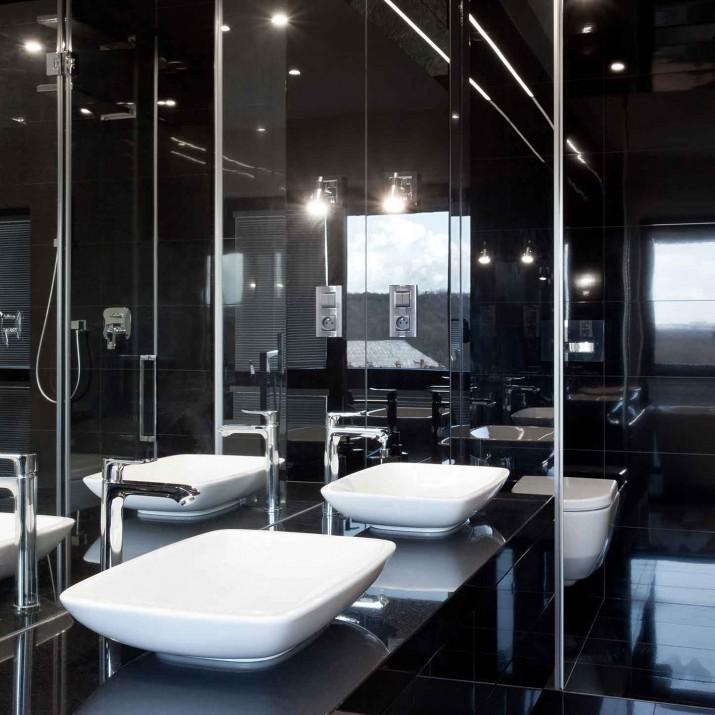 Rodinný dům Unětice - koupelna z kamene, skla a zrcadla.