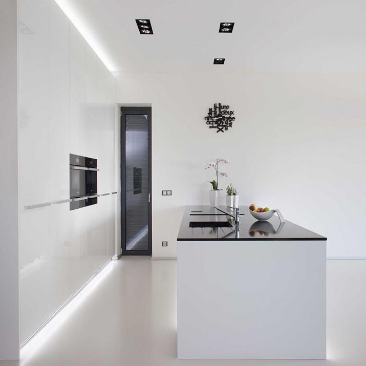 Rodinný dům Žitenice - lakovaná kuchyně ve vysokém lesku s černou kamennou deskou.