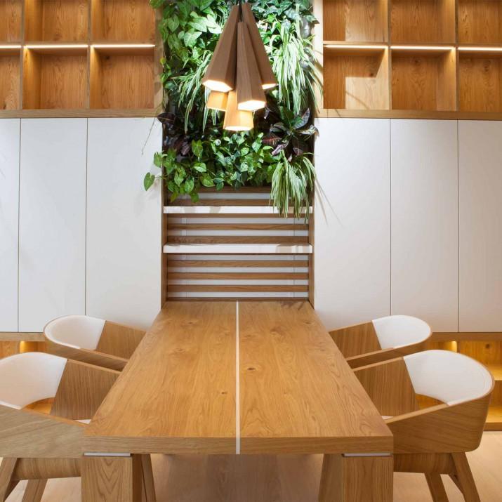 Byt Praha Jarov - jídelní stůl s knihovnou. Vše, i se zelení a osvětlením, ladí dohromady.