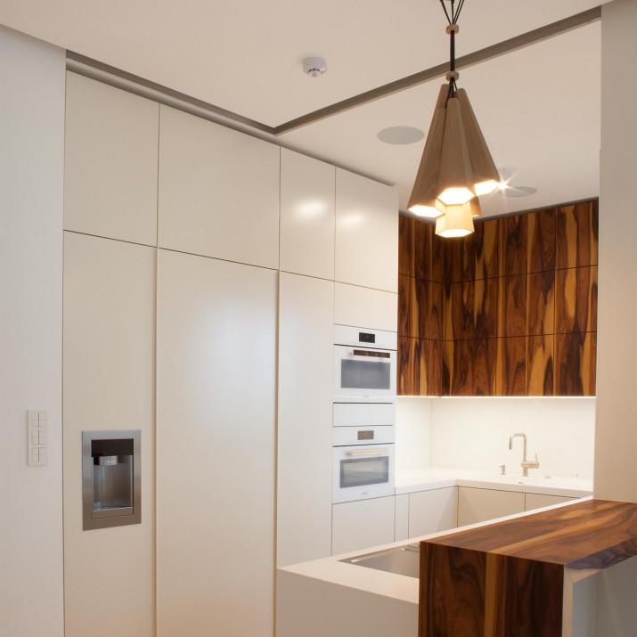 Byt Praha Jarov - kuchyně technologické budoucnosti. Kombinace krémové barvy a palisandrové dýhy z ní dělá i designový skvost. Spotřebiče jsou kombinací BORA a Miele, pracovní deska Corian.