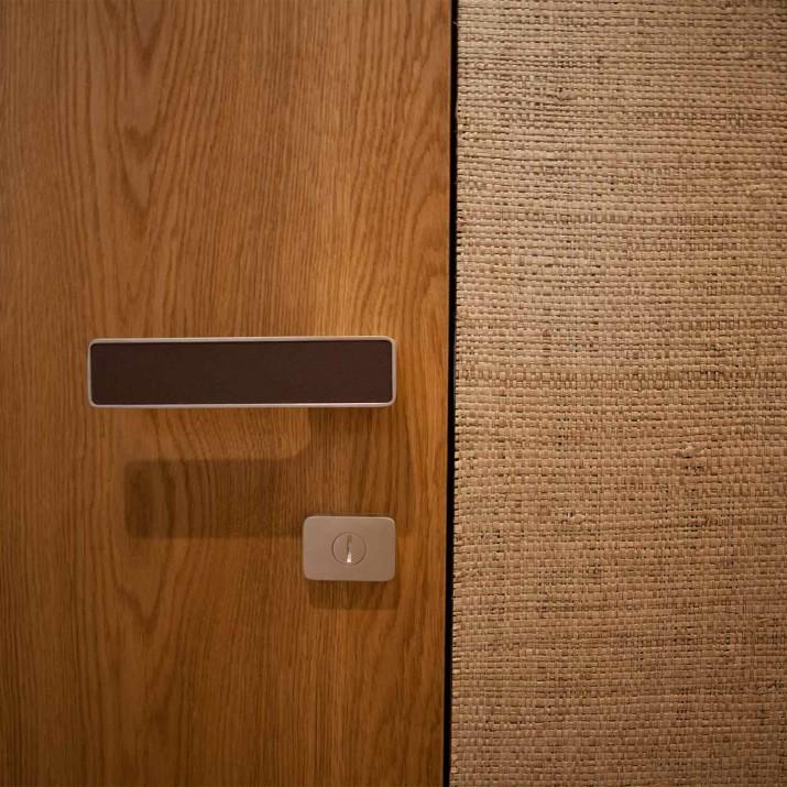 Byt Praha Jarov - detail kliky dveří se skrytou zárubní. Všimněte si výplně kliky z pravé kůže.