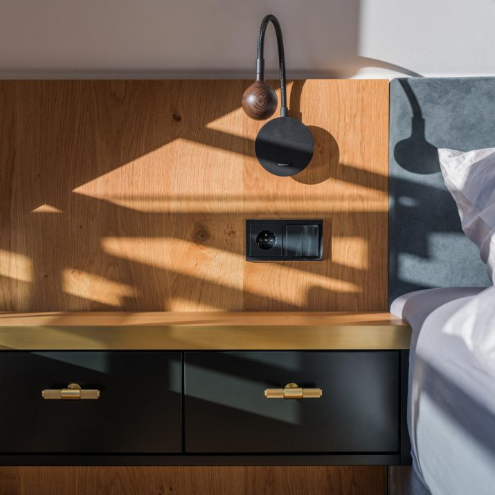 Apartmán Špindlerův Mlýn – Detail nočního stolku se stěnou obloženou dřevem